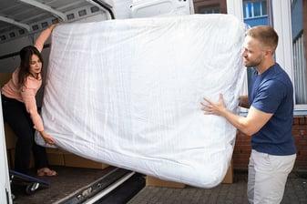 bigstock-Couple-Unloading-Mattress-From-381744140